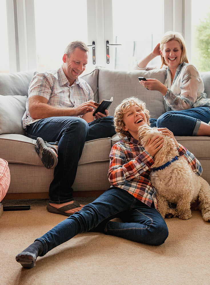 A happy family is sitting in the living room. Their son is sitting on the floor with the family dog licking his face.