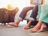 Primer plano de pies descalzos de marido y mujer en el piso de la habitación del hotel.