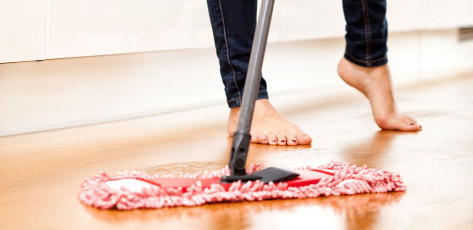 Image of a barefoot woman sweeping the floor with a dry mop.