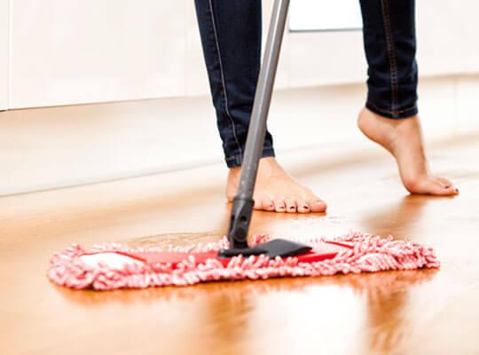 Imagen de una mujer descalza barriendo el piso con un trapeador seco.