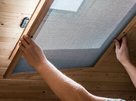 A man installing a screen on a window located on the ceiling.