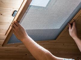 Un hombre instalando un mosquitero en una ventana ubicada en el cielorraso.
