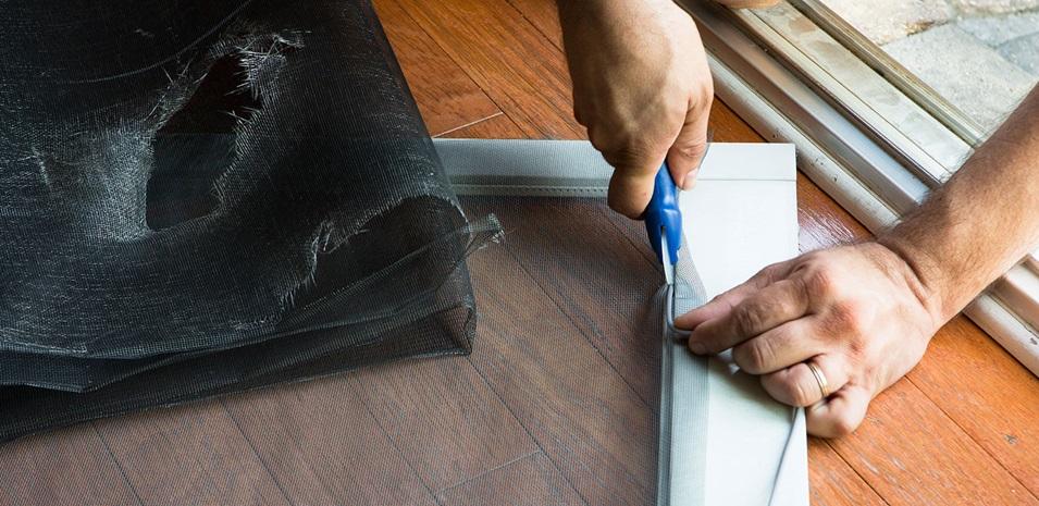Manos de una persona cortando un mosquitero nuevo para una puerta antigua.