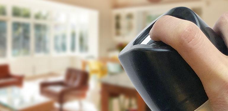 Mano de una persona aplicando rociador en aerosol en una casa.