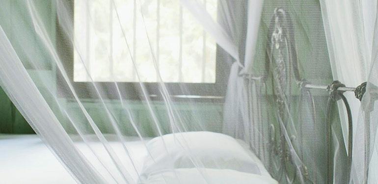 Una cama con un mosquitero sobre ella.