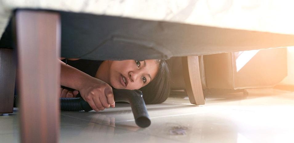 Una mujer agachada aspirando debajo del sofá.