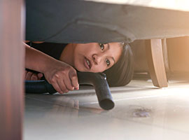 A woman bent down vacuuming underneath her sofa.