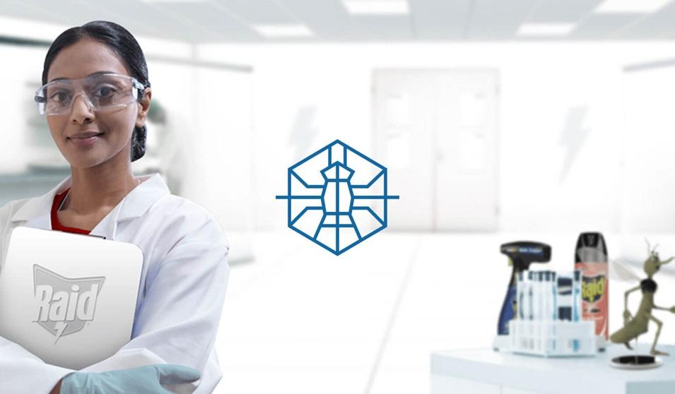 Un entomólogo sonriente, que lleva puesto un guardapolvo de laboratorio y gafas, de pie en un laboratorio del SC Johnson® Institute of Insect Science for Family Health