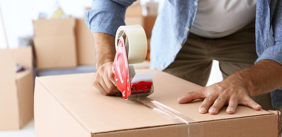 Un hombre sellando una caja de cartón con cinta.