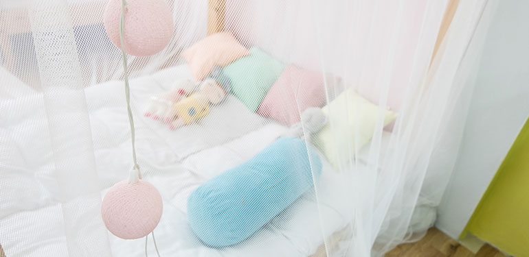 A child's bed covered with a mosquito net.