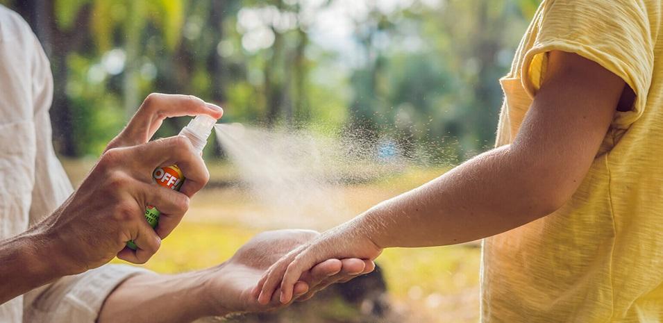 Una madre al aire libre rociando repelente de insectos en el brazo de un niño.