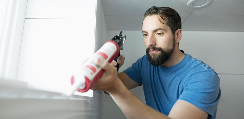A man caulking an indoor window.