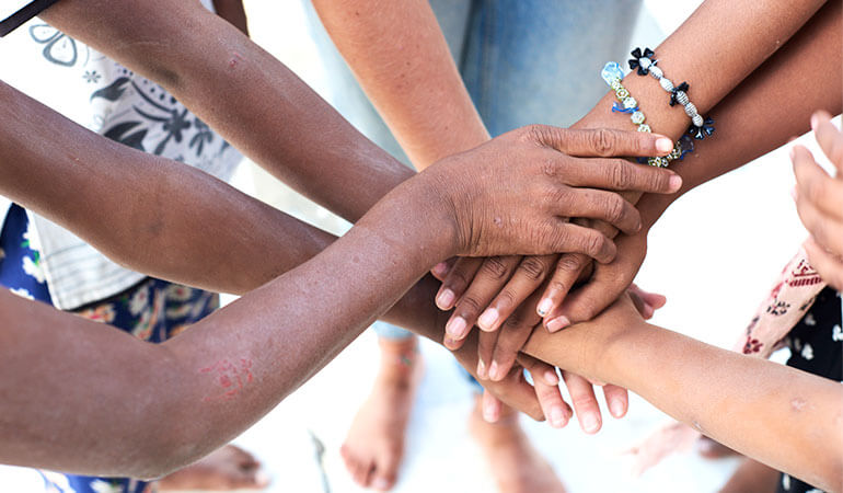 A top view of a group of multiethnic people putting their hands together.
