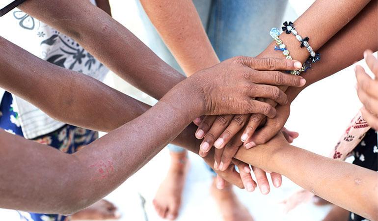 Una vista superior de un grupo de personas multiétnicas tomadas de la mano.