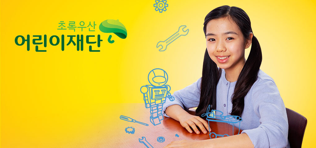 A young girl sitting at a school desk with whimsical illustrations of a robot and tools. This image has a Green Umbrella Children's Foundation logo.