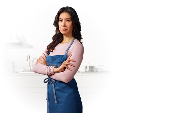 A mom wearing an apron standing in front of a kitchen counter with her arms crossed.